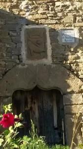 Entrada de la iglesia parroquial de Orante, con su arco conopial y el Crismón, y en su parte superior el Agnus Dei.
