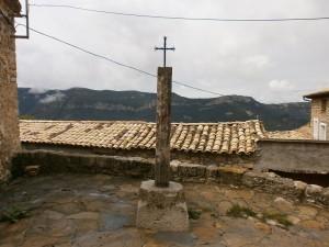 Merli. Crucero de piedra junto a la iglesia parroquial