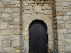 Güel. Puerta de acceso a la ermita, con su crismón