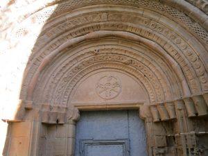 Casbas de Huesca. Crismón en la portada del Monasterio